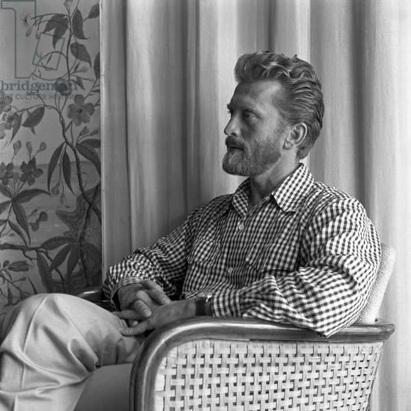 American actor Kirk Douglas portrayed from the side while sitting on a chair, wearing a vichy shirt, his fingers crossed, Venice, 1953