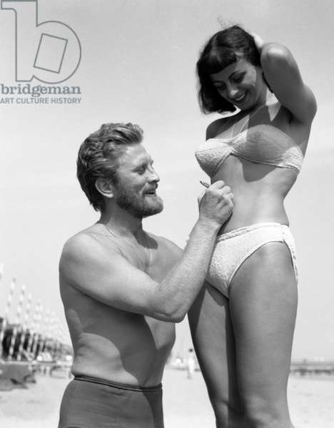 American actor Kirk Douglas, wearing a black swimming suit, standing on his knees, signing on a fan belly with a white swimming suit, on Lido beach, Venice, 1953