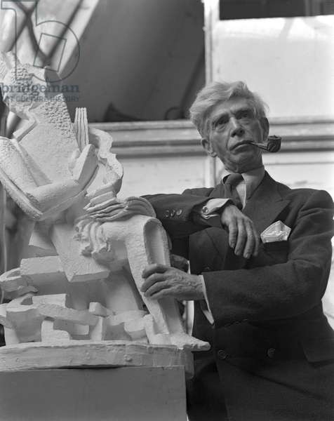 Russian sculptor Ossip Zadkin, wearing a suit and a tie and smoking a pipe, portrayed in his studio while leaning on one of his sculpture, Paris, 1950 (b/w photo)