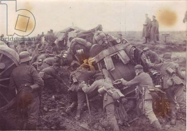 1918 Offensives near Ham, soldiers pushing equipment on muddy ground, under the eye of an officer