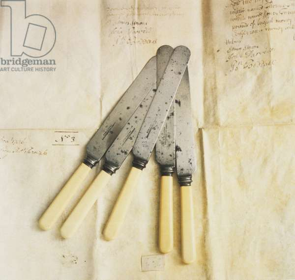Bone-handled table knives on  crumpled paper with notes