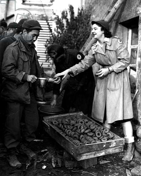 Region of Bruyeres Vosges France November 12, 1944 - An American Red Cross Auxiliary distributes donuts to soldiers of the US Army's 442nd RCT (Regiment Combat Team) at rest after the hard fighting on the Willow Trapin Hill - This infantry unit is made up of Japanese-American volunteers