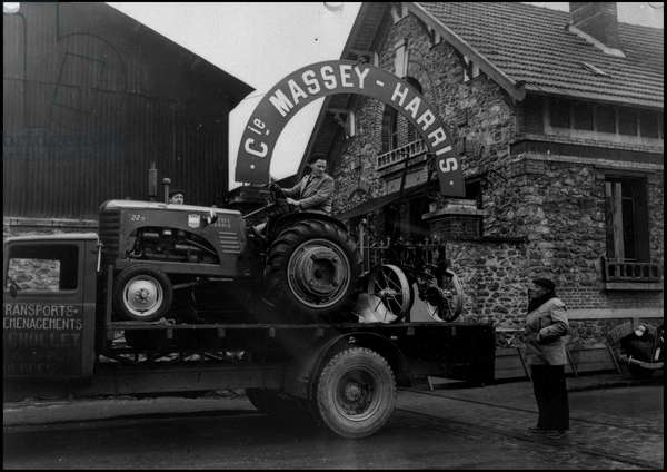 Plan Marshall or European Recovery Program (ERP) (1948-1952): in front of the Massey Harris dealer in Juvisy, one of the 209 American tractors recently arrived in France is unloaded. Juvisy (Seine and Oise), photograph from 1948.