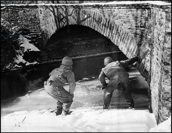 Second World War - Battle of the Bulge (WWII): An officer and a corporal of the Third American Armee looking for possible mines left by German troops during their retreat from Wiltz (Luxembourg) - Photography 23 January 1945