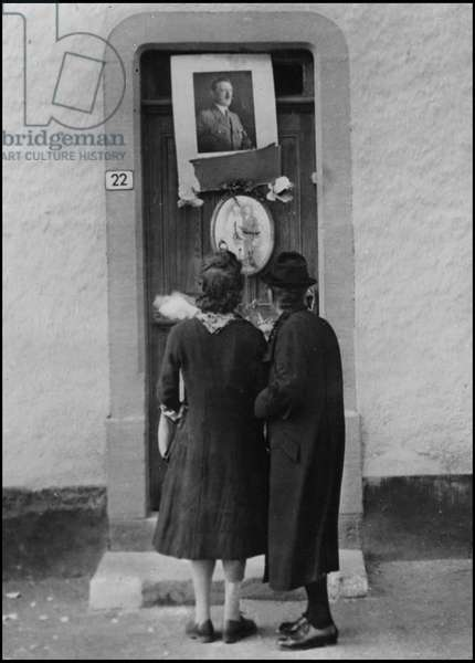 Second World War (1939-1945): two inhabitants of Troisvierges in Luxembourg look at the portrait of Adolf Hitler on the door of their collaborator neighbour who fled to the arrival of Allied soldiers. Photography September 1944.