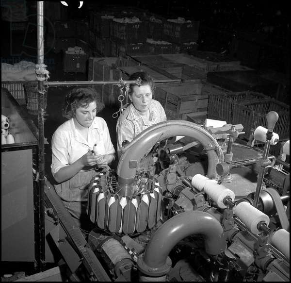 Plan Marshall or European Recovery Program (ERP) (1948-1952): two workers of the Filature Dufour working on an automatic cotton spinning machine supplied by the United States. Armentieres (North), photography around 1950.