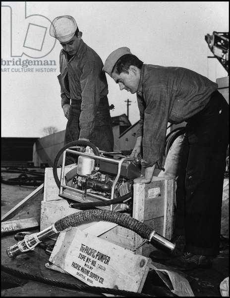 Preparation of the debarkage in Normandy on June 6, 1944 (D Day or D Day): two sailors of the US Navy unlock an engine that must equip a LCT assembly for debarkage. Great Britain, photograph of spring 1944.