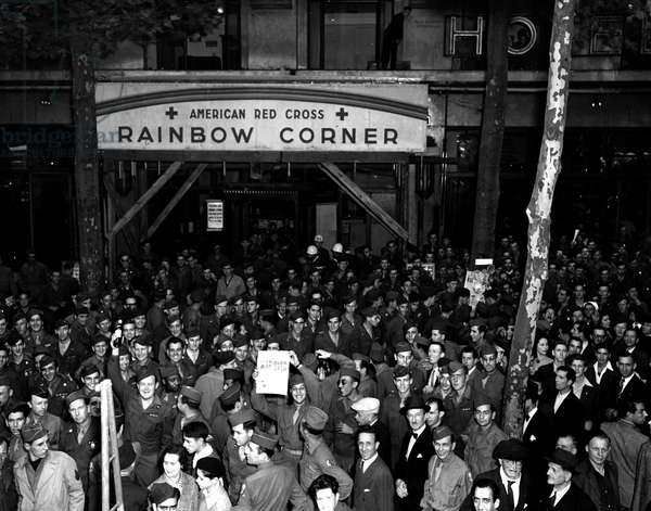 Second World War (1939-1945) - World War II (WWII or WW2): Paris (France) August 14, 1945: A crowd of GI's in front of the Rainbow Corner of the American Red Cross feast the announcement of Japan's unconditional surrender.