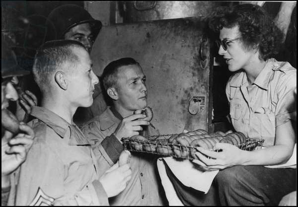 Second World War (1939-1945): an American woman employed by the American Red Cross clubmobile offers doughnuts to two brothers who serve in the same unit of the US Army. Normandy, France, summer 1944. Photography.