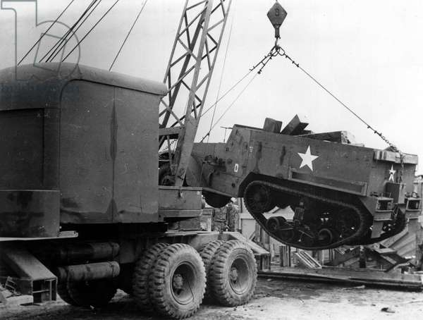 Preparation of the debarkage in Normandy on June 6, 1944 (D Day) (WWII - Normandy landings (D Day) preparations): a crane lifts an armored autochenille (halftrack) which has just arrived in an American army camp in England in preparation for the debarkage - Photography February 1944