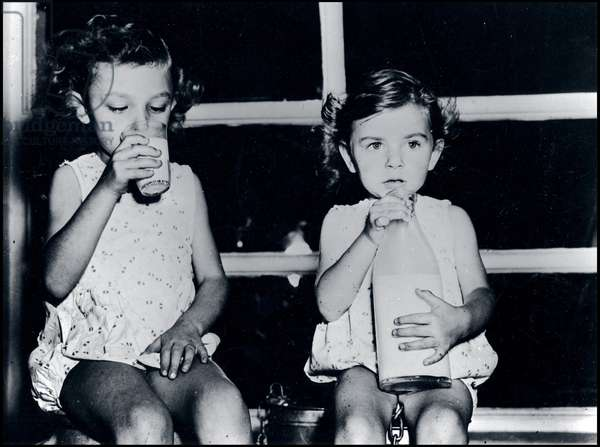 Plan Marshall or European Recovery Program (ERP) (1948-1952): two little girls drink the first bottles of milk received in Lyon through the Economic Cooperation Administration (ECA). Photograph of 1949.