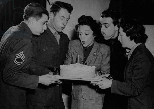 Second World War (1939-1945): Great Britain 1st March 1944: American actress Bebe Daniels, one of the founders of the USO (United Service Organisation) instructs American soldiers to distract all theatres of operations blows the candle of the first anniversary of this organization with two GI's, a US Navy sailor and a Wac.de US Army