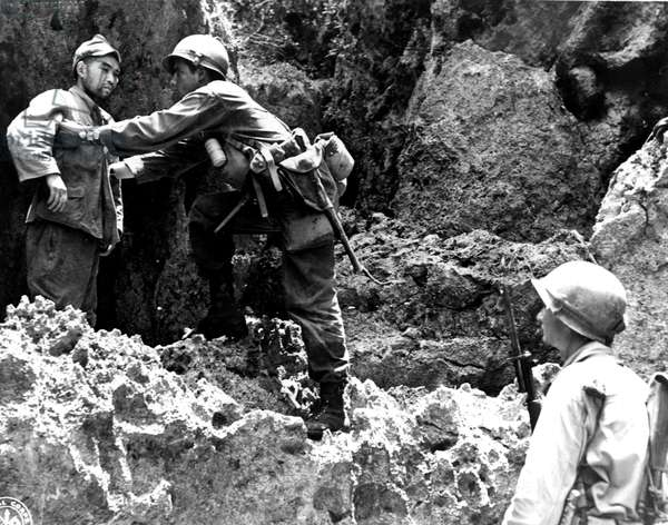 Second World War (1939-1945) - World War II (WWII or WW2): Ryukyu Island Okinawa (Japan) July 14, 1945: A Japanese soldier emerging from a cave surrenders two American soldiers from the 32nd RI of the 10th US Armee.