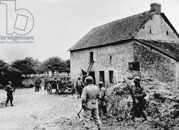Debarking in Normandy on June 6, 1944 (D Day) (WWII - Normandy landings (D Day): American soldiers search a farm in Saint Laurent sur Mer (Saint-Laurent-sur-Mer) in search of a German sniper - Photography 8-9 June 1944
