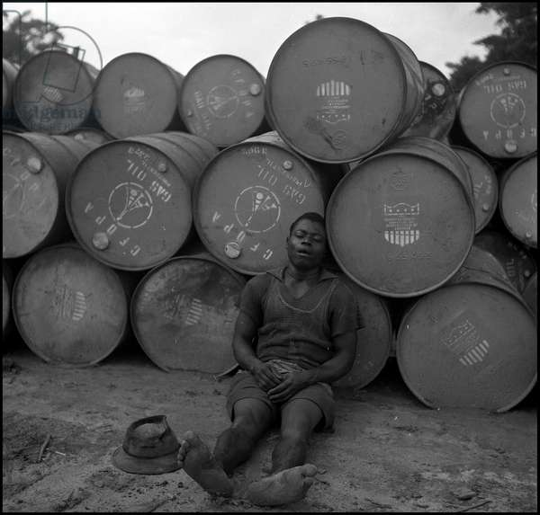 Plan Marshall or European Recovery Program (ERP) (1948-1952): a worker of the SPAEF (Societe Petrolifere de l'Afrique Equatatoriale Francaise) in Gabon relies on barrels of gas oil (provided by Plan Marshall) which allow caterpillars to search for oil. Photography around 1950.