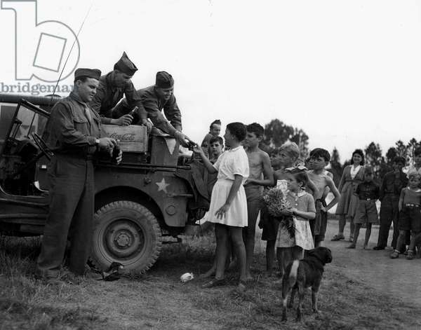 """Second World War (1939-1945) - World War II (WWII or WW2): Near Reims (Marne) France 7 August 1945: a """"regate"""" of auxiliary reservoirs, American soldiers distribute donuts and Coca-Cola to young French"""