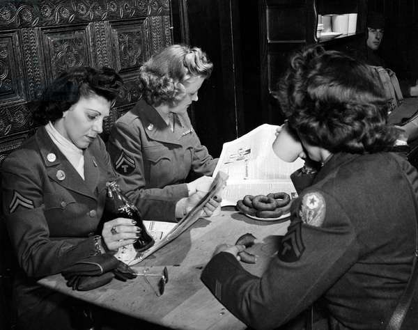 """Second World War (1939-1945) - World War II (WWII or WW2): Brussels (Belgium) August 25, 1945: On leave, these three corporals WAC (Women Army Corps) of the US Army restore themselves at the Ardennais Red Cross Club with doughnuts (doughnuts), Coca-Cola, coffee and reading the newspaper """""""" Stars and Stripes"""""""""""