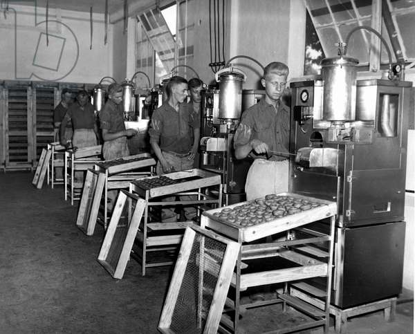 Second World War (1939-1945) - World War II (WWII or WW2): Marseille (France) 18 June 1945: Under the supervision of American soldiers, German prisoners of war work on donuts machines. This plant produces 25000 donuts per day