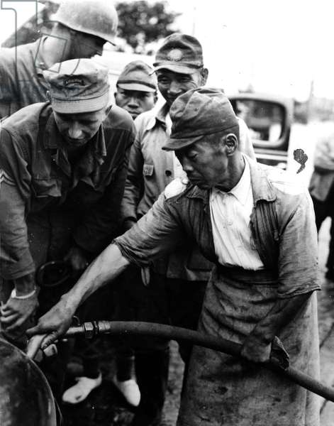 Second World War (1939-1945) - World War II (WWII or WW2): Yokohama (Japan) September 5, 1945: Japanese soldiers put to work according to surrender fill the tank of a US Army transport truck