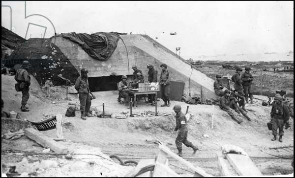 Debarking in Normandy on June 6, 1944 (D Day or D Day): German blockhouse on the beach of Omaha Beach recovered by soldiers of the 1st Infantry Division of the American Army (The Big Red One). Photograph of June 7, 1944.