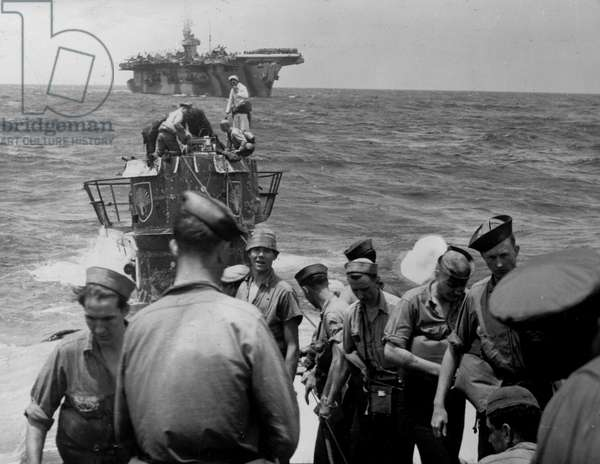 Second World War (1939-1945) - World War II (WWII or WW2): North Atlantic Ocean 4 June 1944 After its capture by the US Navy's Task Group 22.3, the crew of the USS Guadalcanal aircraft carrier (in the background) worked to prevent the shipwreck of the U 505 which they had just farmed. The American Navy found aboard this U-Boot its logbook, an Enigma machine and its codes