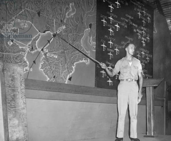 Planning a bombing raid on Japan from Saipan in the Marianas Islands. Capt. Glenn McClure, 500th Bombardment Group, 20th Air Force, pointing to targets on a map of Japan. The air raid's formations of B-29s are on the blackboard behind him. August 13, 1945, several days after the Atomic bombing of Japan, but before the Japanese Surrender. World War 2
