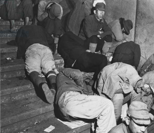 Homeless Japanese in Tokyo, months after Japan's World War II surrender, spend the night on the steps of one of Tokyo's subway stations. Many discharged soldiers are still wearing their military uniforms. Dec. 6, 1945