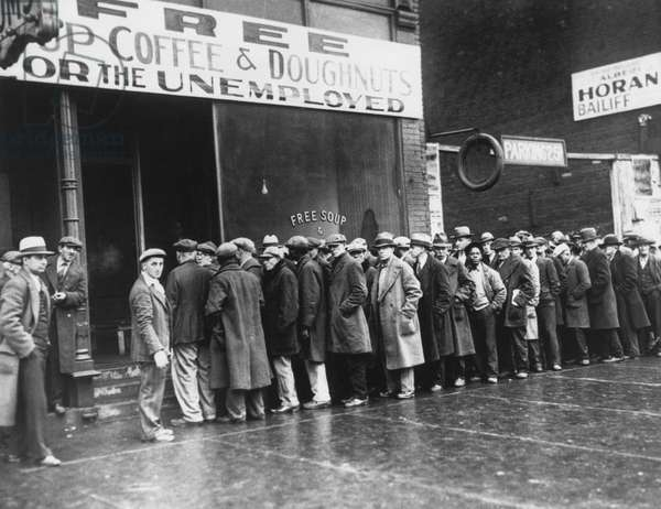 Jobless men in line at a depression era Chicago Soup Kitchen, Feb. 1931. Opened by gangster Al Capone, the storefront sign reads 'Free Soup, Coffee and Doughnuts for the Unemployed'