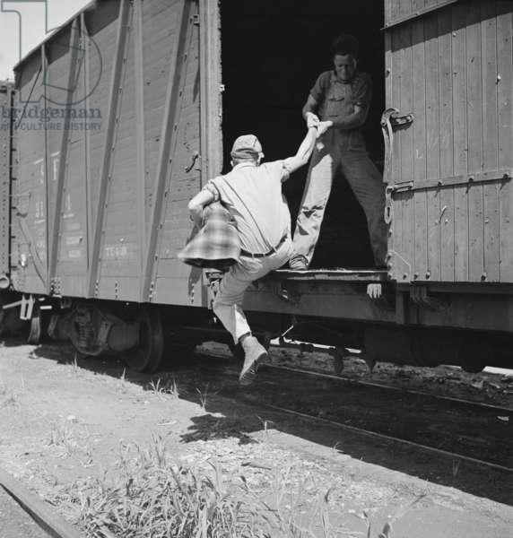 Helping a man hop a freight at Bakersfield, California, 1930s
