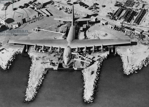 Aerial view of Hughes Flying-boat seaplane under construction at its dock in Long Beach, 1947. The prototype was named 'Hughes H-4 Hercules', but better known as the 'Spruce Goose' because of its wood (birch) construction. Developed as a troop transport, it was six times larger than any aircraft of its time. On Nov. 2, 1947 it made its only test flight, because the war that caused its creation was over