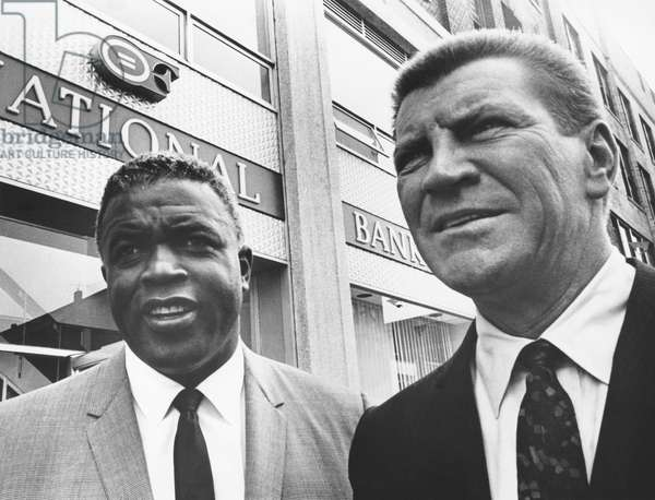 Jackie Robinson, with Robert Preston in front of the Freedom National Bank in Harlem, 1965