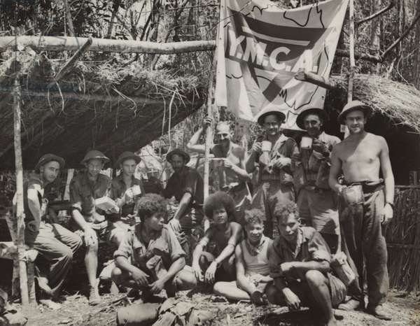 New Guinean natives and Allied troops pause at a YMCA in the jungle. The natives aided the Allied forces against the Japanese by transporting supplies and wounded soldiers through the rain forest. March 1943