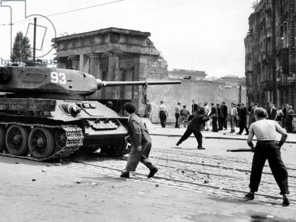Anti-Communist riots in East Germany. An East Berliner throws stones at a Russian tank during the first violent resistance in a Soviet post war satellite state. It began with workers' strike over increased production targets and turned int o widespread protests against the East German state. June 17, 1953