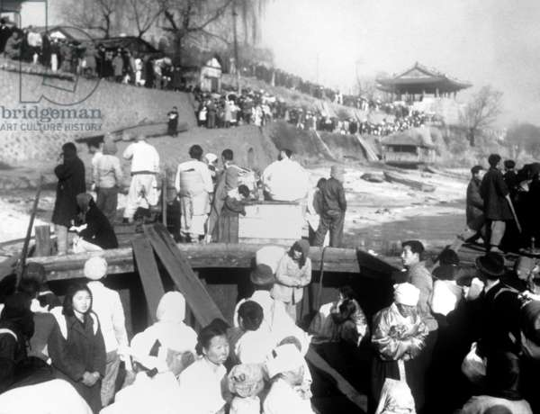 North Korean refugees are evacuated by ferry boats on the Taedong River at Pyongyang, Korea. They are fleeing the North Korean/Chinese troops approaching as the UN troops withdraw to South Korea. Korean War, 1950-53