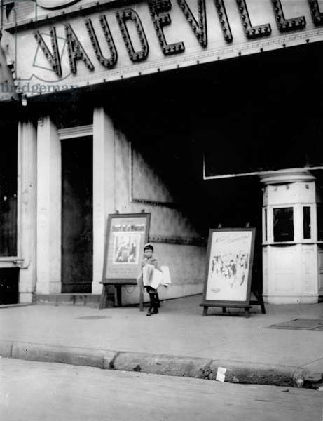 Child labor in front of a movie theater. Harry Silverstein, newsboy, 7 years old, sells papers 8 hours a day at 25 cents per week, doesn''t smoke, visits saloons, Wilmington, Delaware, photograph by Lewis Wickes Hine, May, 1910.