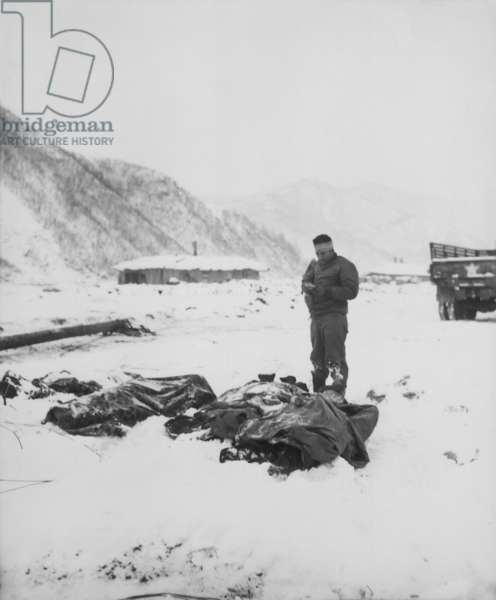 A wounded chaplain reads a memorial service over the snow-covered bodies of dead Marines. At Kotori, Korea, south of the Chosin reservoir where U.S. forces were preparing to withdraw from North Korea. Dec. 4-10, 1950. Korean War, 1950-53