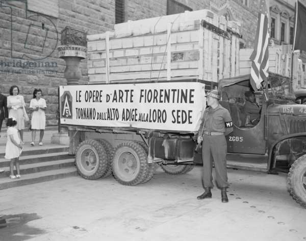 U.S. Soldier guards a truck holding stolen Italian artworks during World War 2. The crated paintings were stolen by the Nazi German army and returned by the U.S. Army's 'Monuments, Fine Arts, and Archives' program. Florence, Italy, July 23, 1945