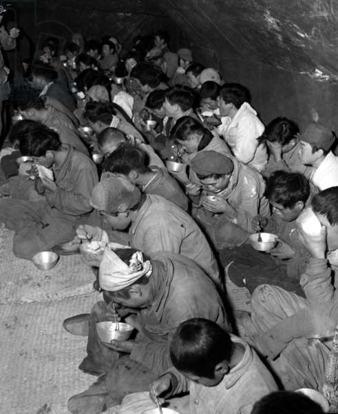 Communist soldiers are fed in the POW stockade, Kurije, Korea. They were captured and brought down from Mt. Chirisan, by soldiers of the ROK (Republic of Korea) Capitol Division. Dec. 12, 1951. Korean War, 1950-53