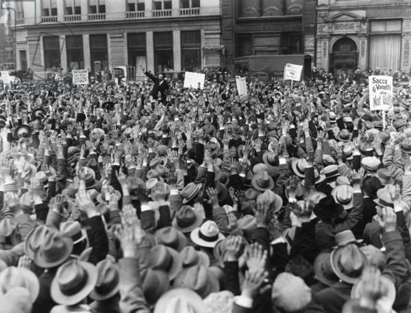 Protest strike advocated at Sacco and Vanzetti meeting at Union Square, NYC. c. April 19, 1927. The Sacco-Vanzetti Defense Committee called for a nationwide strike to protest against the death sentence issued by Judge Webster Thayer on April 9, 1927. People in the crowd raise their hands to agree. A sign reads, 'Sacco 7 Vanzetti are not Guilty' and 'The International Labor Defense Fights to Free Sacco and Vanzetti'.