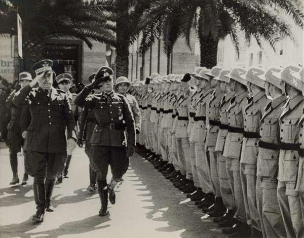 Gen. Italo Gariboldi (left), Italian governor of Libya, reviewing troops with Erwin Rommel. Rommel commanded German Afrika Korps during World War 2. c. 1941