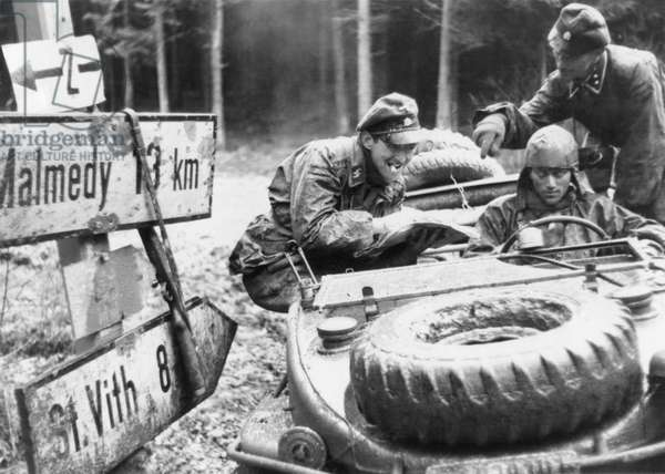 German SS troops with the 1st Panzer division check a highway sign at an Ardennes crossroad. One destination on the sign, Malmedy, would become the site of a Nazi massacre of 84 disarmed American POWs in the Battle of the Bulge. Still from a captured German film. c. Dec. 10-17, 1944. World War 2