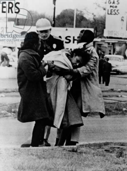 Alabama State Trooper offers no assistance. An unconscious woman is removed by two fellow marchers after she fell in charge of police that broke up first attempted Selma-to-Montgomery on March 7, 1965, afterward called 'Bloody Sunday'