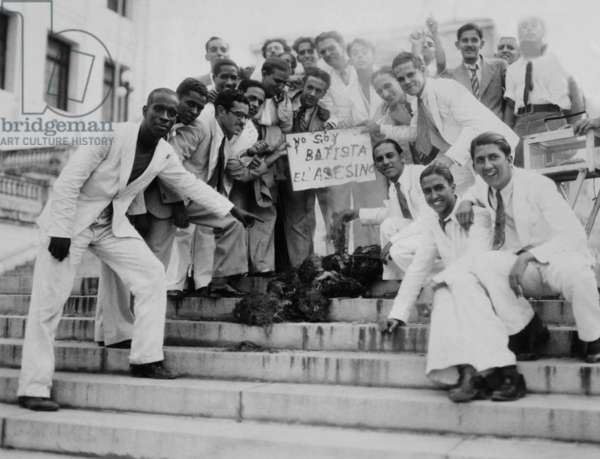 Cuba marks the first anniversary of the coup that overthrew the liberal Cespedes government. This group protested with a burned effigy the coup's leader, Col. Fulgencio Batista. The placards reads, 'I am Batista, Killer'. Sept. 6, 1934