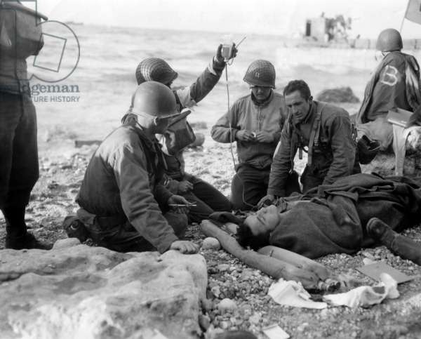 Medics administer a plasma transfusion to a wounded soldier on Omaha Beach on D-day. He is a survivor of a landing craft sunk in the Allied invasion of Normandy. June 6, 1944, World War 2