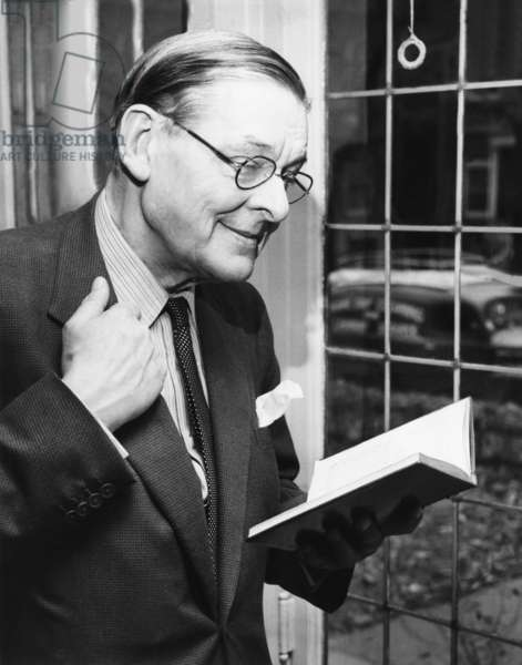 T.S. Eliot, smiling in reminiscence, Nov. 10, 1959. He is holding a book containing some of his early works during a press conference at the University of Chicago. Eliot conducted a reading of his works on behalf of the Modern Poetry Association which sponsors 'Poetry Magazine'. Eliot had his first poem published in the Magazine in 1915. -
