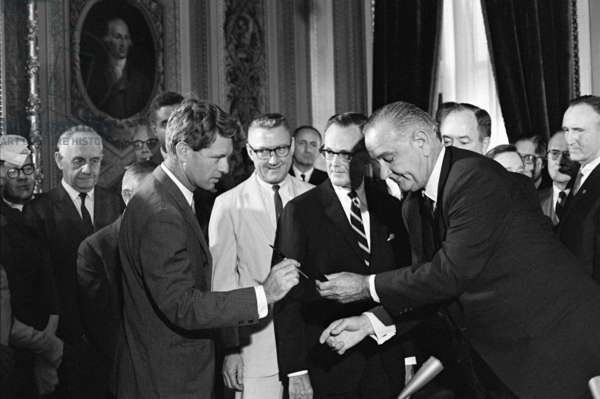 1965 Voting Rights signing ceremony. President Lyndon Johnson handing a signing pen to Robert Kennedy as others look on. August 6, 1965