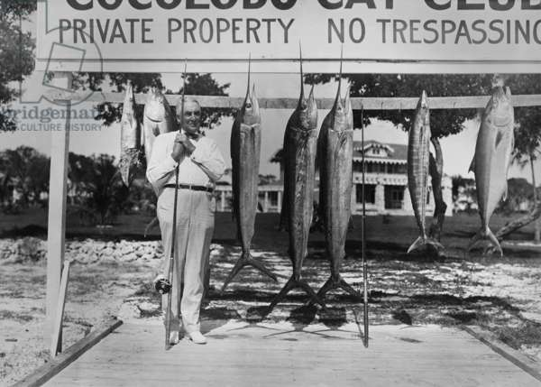Warren Harding with fishing rod and fish at Cocolobo Cay Club, Adams Key, Florida. c. 1921-23