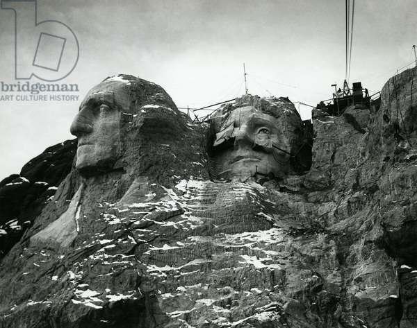 Mount Rushmore sculptures of Washington and Jefferson with finished faces c. 1935. Their hair is still in rough form. Photo by Charles d'Emery