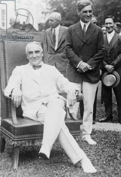 President Warren G. Harding, seated on chair presented to him by newspaper editors, outside the White House. 1921