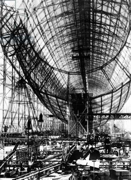 Hindenburg Airship under construction. The almost complete steel frame at the Zeppelin works at Friedrichshafen, Germany. Mechanics work in the right foreground. Nov. 24, 1934.